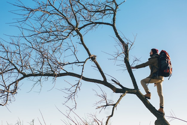 Hombre inconformista viajando con mochila, de pie en un árbol contra el cielo, con chaqueta abrigada, turista activo, explorando la naturaleza en la estación fría