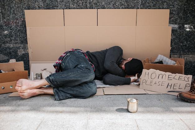 Hombre indefenso e indefenso está acostado sobre el cartón en el piso de concreto y durmiendo