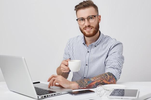 Un hombre independiente encantador con barba espesa, usa anteojos, tiene tatuajes, trabaja de forma remota
