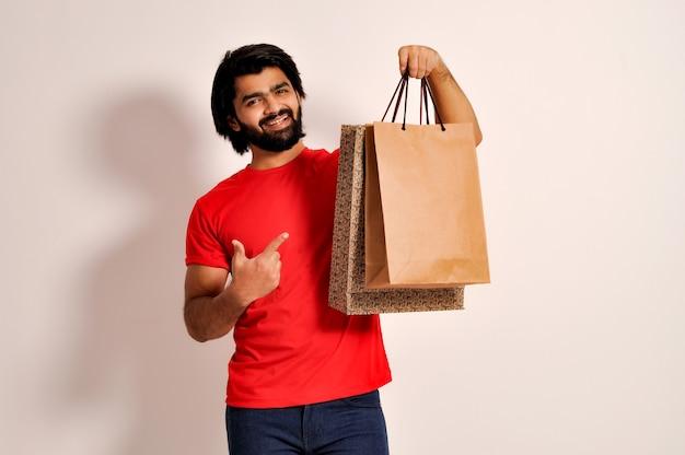 Hombre indio caminando con bolsas de la compra sonriendo mientras hace compras y apuntando con la mano