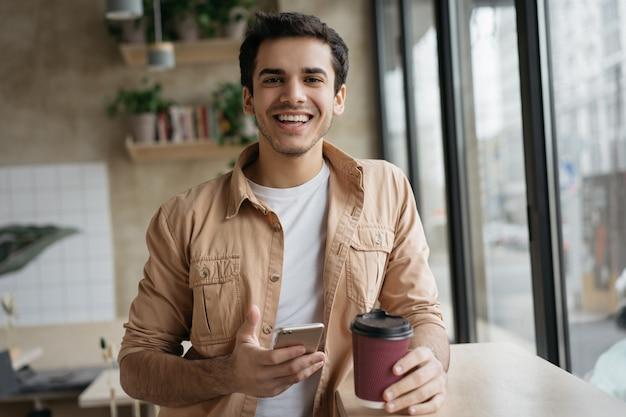 Hombre indio feliz sosteniendo la taza de café y teléfono inteligente mirando a cámara, de pie en la cafetería