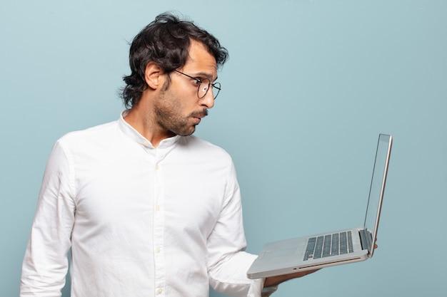 Hombre indio hermoso joven que sostiene una computadora portátil. concepto de negocio o redes sociales