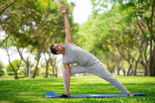 Hombre indio inspirado que hace asanas de la yoga en parque de la ciudad. joven ciudadano haciendo ejercicio al aire libre