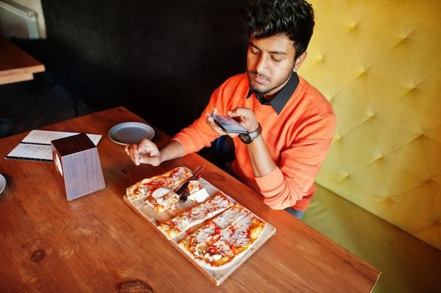 Hombre indio joven confidente en suéter naranja sentado en la pizzería, comer pizza y hace fotos en su teléfono.