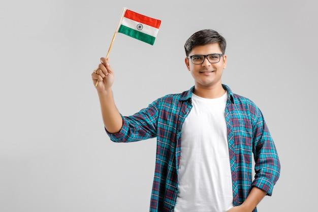 Hombre indio joven que sostiene la bandera india en la mano