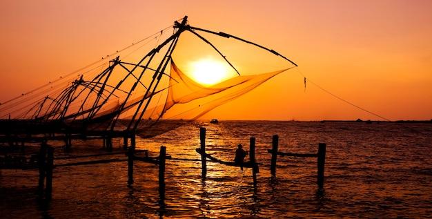 Hombre indio que pesca bajo las grandes redes chinas en cochin, kerela, india