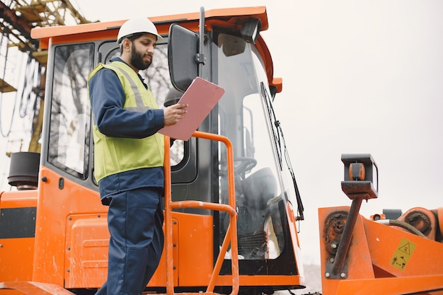 Hombre indio trabajando. hombre con chaleco amarillo. hombre cerca del tractor.