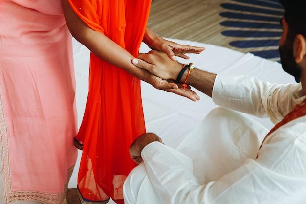 Hombre indio en traje blanco y mujer vestida de salmón están tomados de la mano