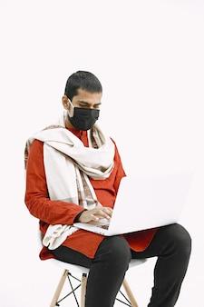 Hombre indio en traje nacional que trabaja con la computadora portátil en una pared blanca.