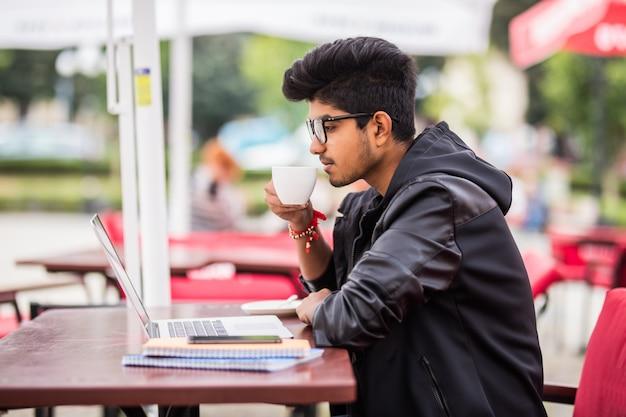 Hombre indio usando laptop mientras bebe una taza de café en un café callejero al aire libre