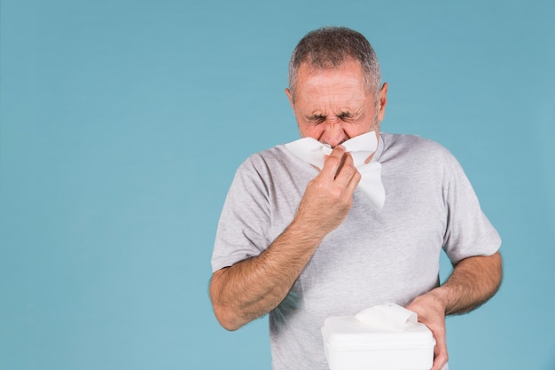 Hombre infectado con resfriado y gripe soplando su nariz en el tejido.