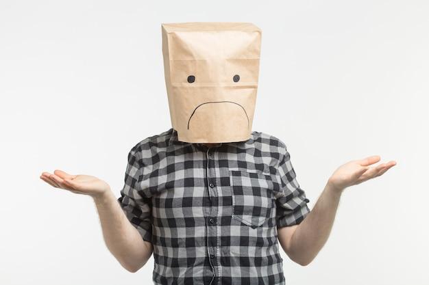 Hombre infeliz con emoticon triste delante de la bolsa de papel en la cabeza sobre fondo blanco.