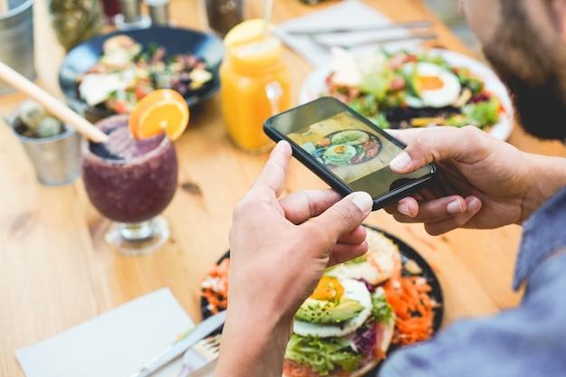 Hombre influyente comiendo brunch mientras hace videos y fotos del plato con el teléfono móvil en un bar de moda