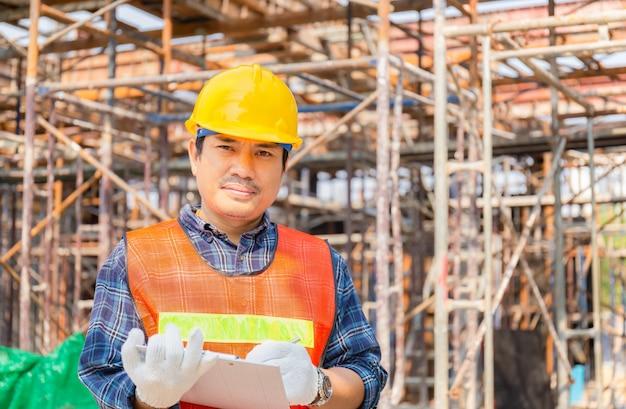 Hombre ingeniero comprobación y planificación de proyectos en el sitio de construcción, hombre sujetando la lista de verificación del portapapeles sobre fondo azul.