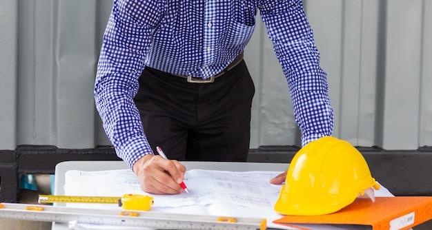 Hombre ingeniero mirando plan de proyecto de plan de papel cerca del contenedor en el sitio de construcción. trabajando al aire libre para ver el progreso del nuevo proyecto de construcción.
