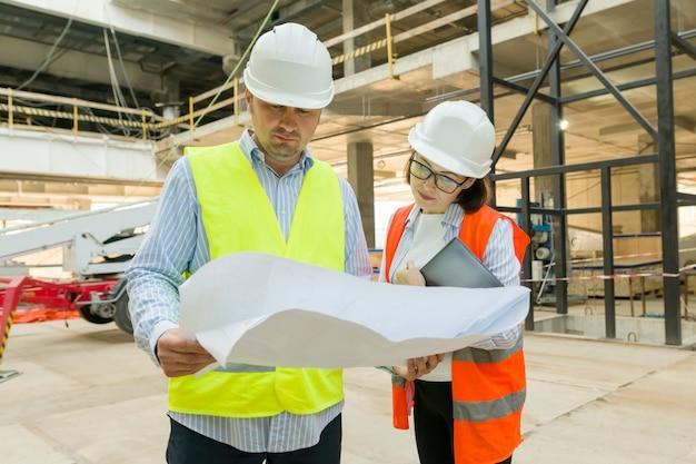 Hombre ingeniero y mujer arquitecto en un sitio de construcción