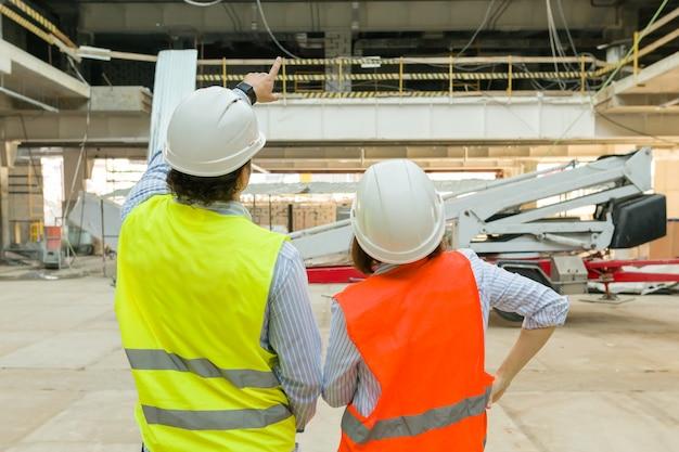 Hombre ingeniero y mujer arquitecto en un sitio de construcción.