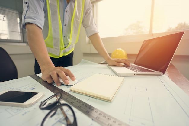 Hombre ingeniero que trabaja con una computadora portátil y planos que bosquejan un proyecto de construcción