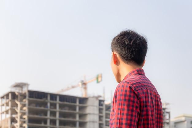 Hombre ingeniero revisando y planificando proyecto en sitio de construcción, hombre mirando en el sitio de construcción