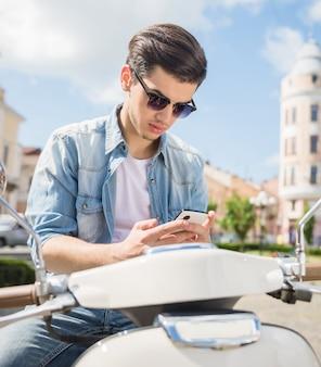 Hombre ingenioso guapo sentado en scooter y usando el teléfono.
