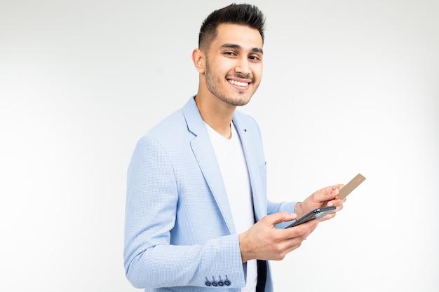 Un hombre ingresa datos con una tarjeta de crédito en un teléfono móvil para realizar una compra a través de internet sobre un fondo blanco.