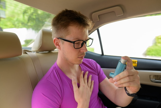 Hombre con inhalador para el asma en el asiento trasero del coche