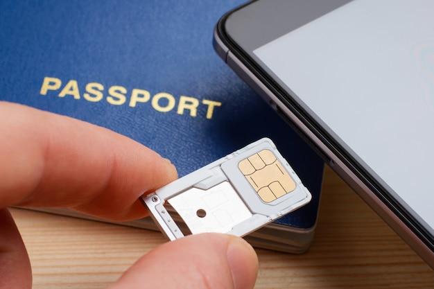 Hombre insertando bandeja para tarjeta sim y tarjeta de memoria micro sd al teléfono móvil cerca del pasaporte
