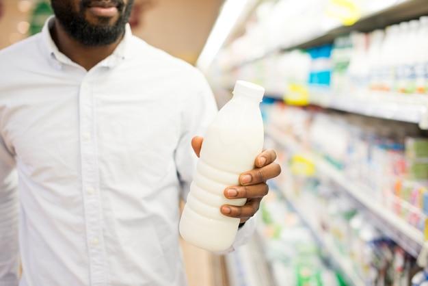 Hombre inspeccionando botella de leche en la tienda de comestibles