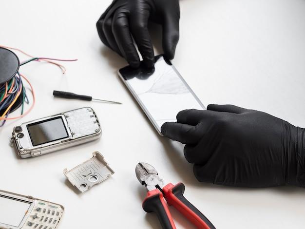 Hombre inspeccionando teléfono con pantalla rota