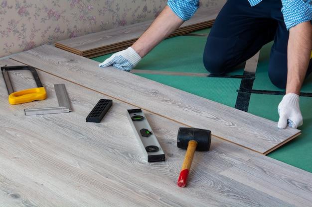 El hombre instala nuevos pisos laminados