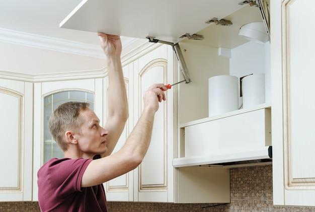 Hombre instalando muebles de cocina