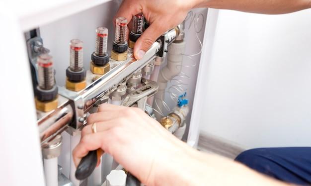 El hombre está instalando el sistema de calefacción en la casa.