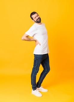 Hombre integral con barba sobre una pared amarilla aislada que sufre de dolor de espalda por haber hecho un esfuerzo