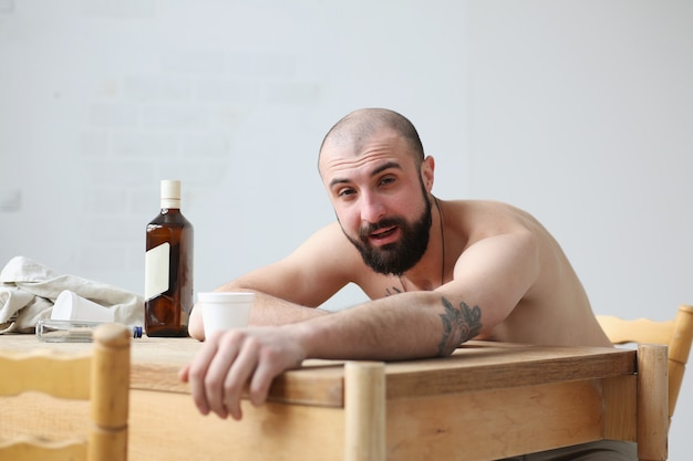 El hombre con el intelecto nublado por el alcohol o las drogas mira a la cámara.