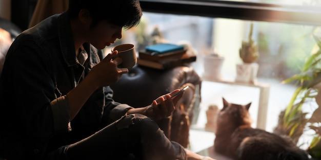 Un hombre inteligente bebiendo café caliente mientras usa un teléfono inteligente en la mano y sentado en el sofá de cuero junto a su adorable gato sobre una cómoda sala de estar como fondo.