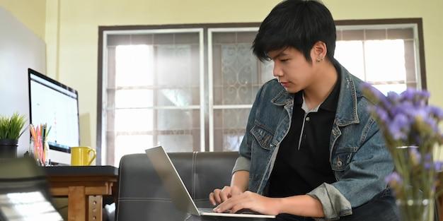 Hombre inteligente en camisa de jean escribiendo en la computadora portátil que se pone en su regazo mientras está sentado y se relaja en el sofá de cuero negro sobre la cómoda sala de estar