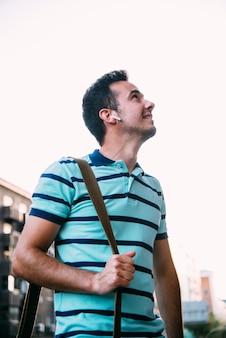 Hombre inteligente guapo con teléfono móvil escuchando música en la calle. concepto de comunicación