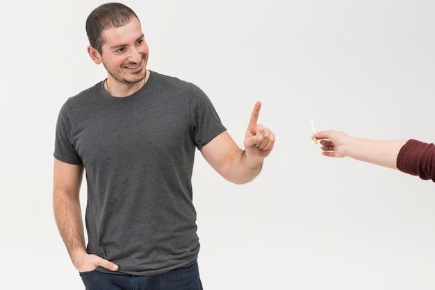 Hombre inteligente sonriente que dice no al cigarrillo ofrecido por una persona contra el fondo blanco