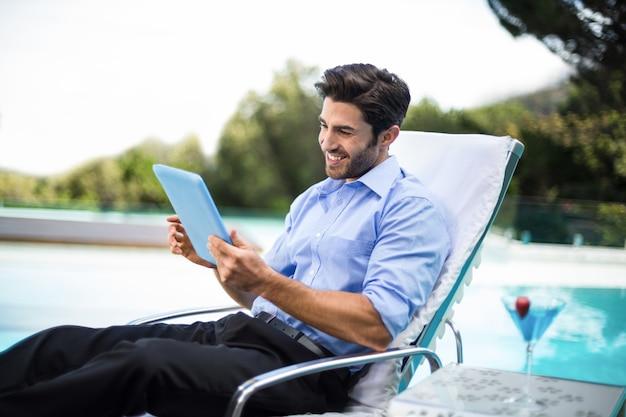 Hombre inteligente con tableta digital junto a la piscina