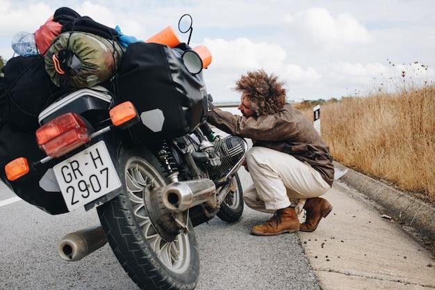 El hombre intenta arreglar la moto al costado de la carretera