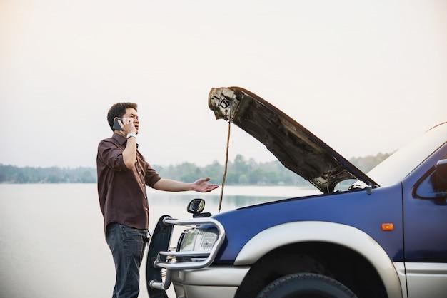 El hombre intenta solucionar un problema con el motor de un automóvil en una carretera local chiang mai tailandia