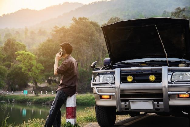 El hombre intenta solucionar un problema de motor de automóvil en una carretera local