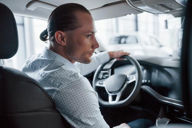 Hombre intentando coche nuevo en el salón durante el día. comprar vehículo nuevo