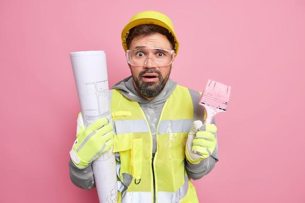 Hombre involucrado en trabajos de renovación de viviendas suministros servicio de reparación profesional tiene pincel de pintura hace planos arquitectónicos usa ropa protectora