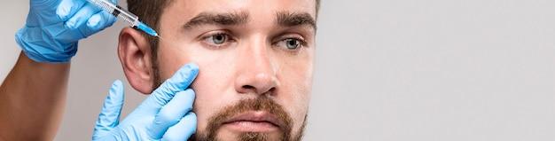 El hombre se inyecta en la cara con espacio de copia