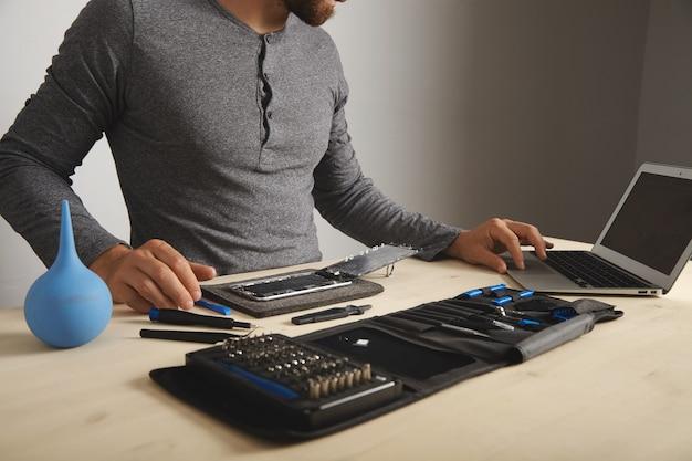 Hombre irreconocible busca guías en internet mientras repara su smartphone, cambia pantalla y batería