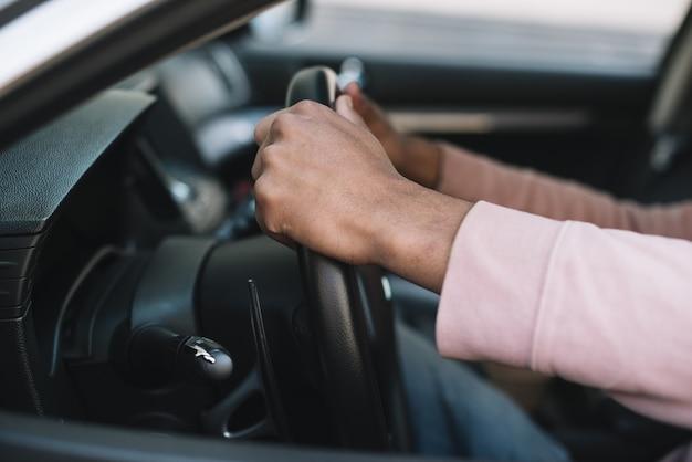 Hombre irreconocible conduciendo cerca