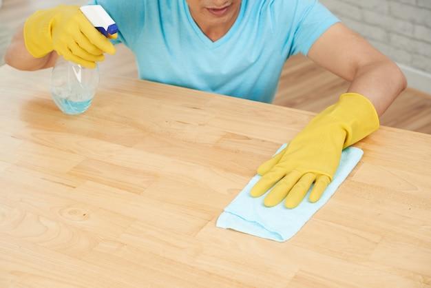 Hombre irreconocible en guantes de goma rociando mesa y limpiando con tela