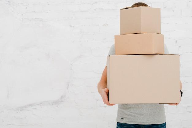 Hombre irreconocible llevando cajas