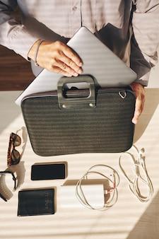 Hombre irreconocible que pone una computadora portátil y dispositivos en el maletín
